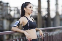 Chinese woman listening to music after exercising on street — Stock Photo