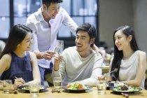 Asian friends clinking glasses at dinner in restaurant — Stock Photo
