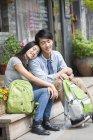 Китайська пара, відпочиваючи на сходи з рюкзаками — стокове фото