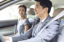 Homme d'affaires chinois au volant de voiture avec petite amie — Photo de stock