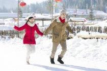 Китайська пара холдингу руки і працює в снігу — стокове фото