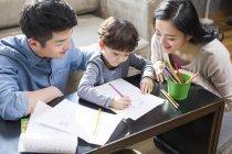 Asiatischen Eltern Sohn bei den Hausaufgaben zu helfen — Stockfoto