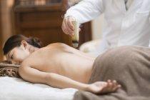 Médecin donnant femme moxibustion sur table de massage — Photo de stock