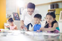 Chinese children painting in art class with teacher — Stock Photo