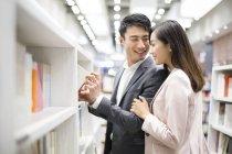 Couple chinois choisissant des livres en librairie — Photo de stock