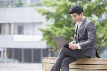 Homme d'affaires chinois travaillant avec portable sur banc — Photo de stock