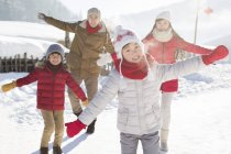 Chinese family posing with arms outstretched in snow — Stock Photo