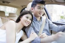 Chinese woman holding male arm in car — Stock Photo