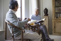 Senior Chinese men discussing while reading books in living room — Stock Photo