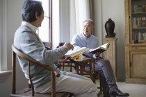 Seniors hombres chinos discutiendo mientras que la lectura de libros en sala - foto de stock