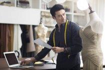 Asian fashion designer working in studio with laptop — Stock Photo