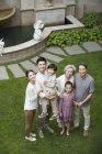 Vista di alto angolo della famiglia cinese che osserva in su prato verde — Foto stock