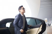 Asiatischer Geschäftsmann steigt im Flughafen-Terminal aus Auto — Stockfoto