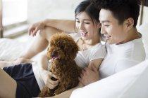 Молодая китайская пара играет дома с домашним пуделем — стоковое фото