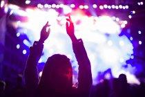 Silueta femenina con brazos levantados en concierto de música - foto de stock