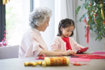 Granddaughter and grandmother making Chinese New Year paper-cut — Stock Photo