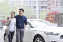 Mature chinese couple walking on street by car — Stock Photo
