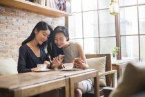 Китайський подруг, використання смартфонів в кафе — стокове фото