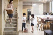 Chinesische Kinder fegen Fußboden, während Mutter Wäsche hält — Stockfoto