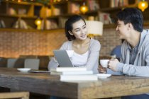 Chinese man and woman talking in cafe — Stock Photo