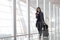 Asiática mujer tirando de equipaje en aeropuerto lobby - foto de stock