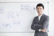Uomo d'affari cinese in piedi davanti alla lavagna bianca — Foto stock