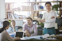Architectes, discutant de travail dans office tandis que l'homme d'âge mûr souriant et regardant à huis clos — Photo de stock
