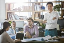 Architects discussing work in office while mature man smiling and looking in camera — Stock Photo