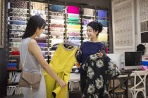 Chinese clothing store owner helping customer choosing dresses — Stock Photo