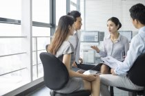 Chinese business team sitting and talking in meeting — Stock Photo