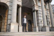Homem de negócios chinês em pé na construção de escadaria na cidade — Fotografia de Stock