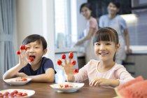 Irmãos chineses jogando com tomates-cereja com os pais no fundo — Fotografia de Stock