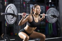 Chinese woman lifting barbell at gym — Stock Photo