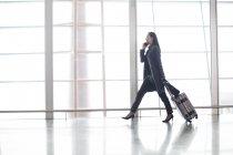 Femme asiatique marchant et parlant au téléphone à l'aéroport — Photo de stock