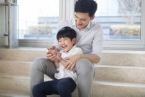 Chinese father tickling son in living room — Stock Photo