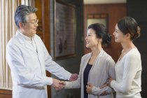 Mature chinese doctor shaking hands with patient — Stock Photo