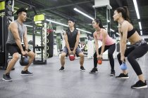 Asian adults working with trainer at gym — Stock Photo