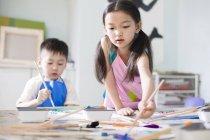 Niños chinos pintando en clase de arte - foto de stock
