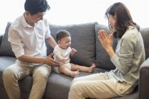 Chinese mother clapping while looking at sitting baby boy — Stock Photo