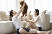 Chinesisches Ehepaar mit Haustier Pudel zu Hause spielen — Stockfoto