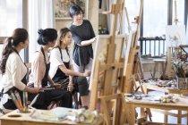 Femmes asiatiques avec professeur d'art travaillant en studio — Photo de stock