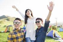 Amigos chinos posando con los brazos levantados en el campamento festival - foto de stock