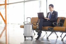 Chinese businessman using laptop in airport waiting room — Stock Photo