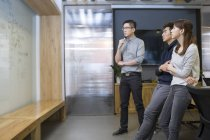 Chinese office workers looking at whiteboard in board room — Stock Photo