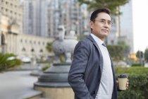 Empresário chinês segurando café e olhando para a vista na cidade — Fotografia de Stock