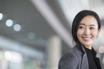 Retrato de mujer asiática sonriendo y mirando hacia otro lado - foto de stock