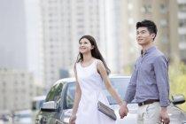 China pareja cogidos de la mano frente a coche - foto de stock