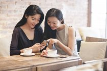Chinese female friends using smartphone in coffee shop — Stock Photo