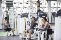 Asiáticos adultos utilizando máquinas de ejercicio en el gimnasio - foto de stock