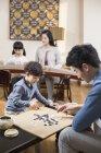 Actividades de lazer família asiática com instrumento musical e jogo de Go — Fotografia de Stock